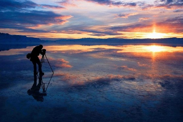 Man taking picture of a sunset over water