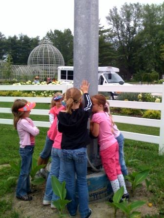 Children gathered at the base of a wind turbine.
